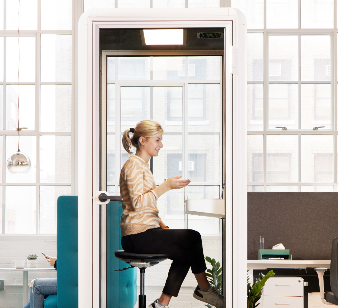 Employee video conferencing from White PoppinPod Kolo 1 with Stool in open office